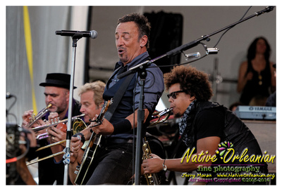 "bruce_springsteen_jazz_fest_jm_050314_004On Bruce Springsteen, I've seen ""The Boss"" 3 times now at Jazz Fest, all most memorable but for distinctly different reasons. The first was right after Katrina in 2006 when Bruce Springsteen brought his freshly formed Seeger Sessions Band to New Orleans bringing his storytelling, musicianship and healing powers to a down ,but no way near out, population in New Orleans, soothing the crowd with a special folk infused show, which was new for him yet amazing considering the collective conscience at that time......I specifically recall ""My City of Ruins.""(with tears while writing) being a watershed moment in the show......The show reminded me of church, and I never left my pew........The second time I saw Springsteen, he was with the E-Street Band infusing the show with emotions that reflected a recovery, less somber more upbeat...... and that was a great show too......and then this years, the most powerful(on the positive) one of the three. I was backstage after shooting Voice of the Wetlands Allstars and saw Bruce and the Band come out of a semi where they gathered for a minute , then in single file all following ""The Boss"" whose gait was one of supreme confidence.......ready to go kick some rock'n roll ass for a few hours.....which they did...... I wandered with Johnny Sansone and Christy up to the right side where we could see pretty good. That's when I noticed the shit eatin grin on Springsteen's face, the dude was havin just a ball and wore it on his sleeves(as he always has). Fortunately I was able to capture a few nice images of ""The Boss"" that convey something close to what I attempt to describe......Jerry ;-) ©2005-2014 Jerry Moran Native Orleanian LLC Many more pics and a musical slideshow will be added to <a target=""_blank"" href=""http://www.nativeorleanian.org/new_orleans_jazz_and_heritage_festival_2014"">http://www.nativeorleanian.org/new_orleans_jazz_and_heritage_festival_2014</a>"